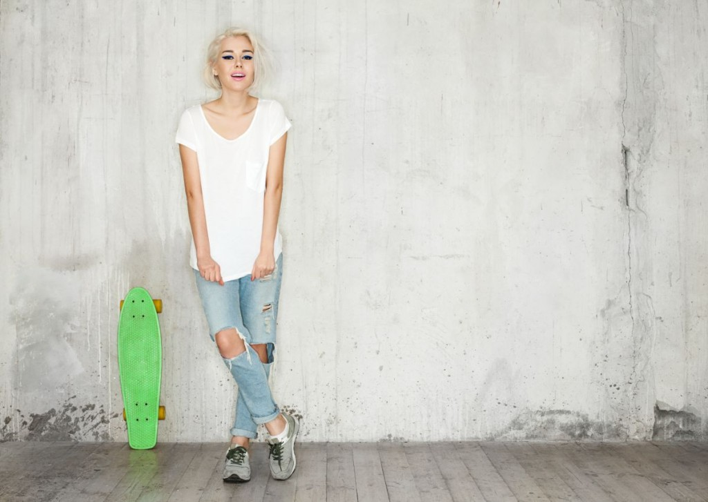 Blonde with a skate in a white T-shirt against the background of a concrete wall